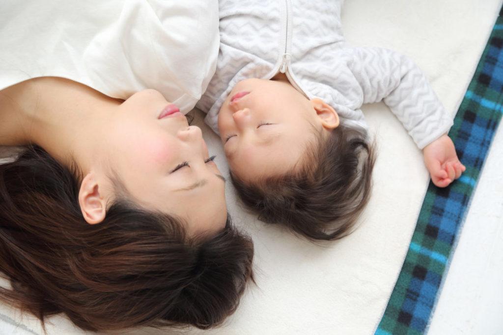 寝ている子どもとお母さん