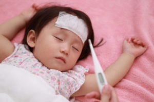 熱が出て体温を測る子ども
