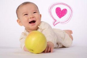 笑顔の赤ちゃんと青りんご